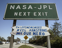In this photo taken on Sunday, Aug. 26, 2012, a handmade sign honoring astronaut Neil Armstrong is hung under a freeway off ramp sign at the NASA-JPL exit on the CA-210 Freeway in Pasadena, Calif. Armstrong, the first man on the moon, who inspired millions with his moonwalk died Saturday, Aug. 25, 2012. He was 82. (AP Photo/Damian Dovarganes)