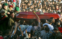 FILE - In this Nov. 12, 2004 file photo, the coffin of Yasser Arafat is carried through the crowd of Palestinian mourners to be lowered into the grave at his compound in the West Bank town of Ramallah. A former Israeli official on Wednesday, Aug. 29, 2012 denied suspicions that Israel poisoned Palestinian leader Yasser Arafat as France prepared to begin an investigation into his possible murder following a Swiss lab's claim that it found traces of a deadly substance on his belongings. (AP Photo/David Guttenfelder, File)