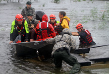 Members of the Swift Water Rescue Team rescue stranded employees of WQRZ radio station in the Shoreline Park area of Bay St. Louis, Miss., during Hurricane Isaac on Wednesday,  Aug. 29, 2012. Isaac was packing 80 mph winds, making it a Category 1 hurricane. It came ashore early Tuesday near the mouth of the Mississippi River, driving a wall of water nearly 11 feet high inland and soaking a neck of land that stretches into the Gulf.  (AP Photo/Sun Herald, John  Fitzhugh)