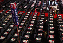 A volunteer places pamphlets on chairs in Montana's delegation seating area before the start of the Republican National Convention in Tampa, Fla., on Tuesday, Aug. 28, 2012. (AP Photo/Lynne Sladky)