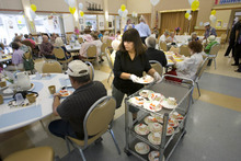 Paul Fraughton | Salt Lake Tribune Lillian Brito, a volunteer at the Taylorsville Senior Center, passes out pieces of cake to seniors eating their lunch at the center. The special treat was part of the celebration of the 100,000th lunch served there. Wednesday, August 29, 2012