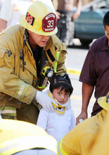 A Los Angeles City firefighter assists a child, one of eight people injured when a car sped onto a sidewalk and plowed into a group of parents and children outside Main Street Elementary school, Wednesday Aug. 29, 2012 in Los Angeles. The crash occurred at 2:50 p.m., shortly after school had let out for the day, according to a statement from the Los Angeles Unified School District. (AP Photo/La Opinion, J. Emilio Flores)