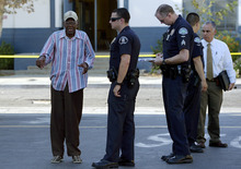 Preston Carter, left, 100, talks with police officers after his car went onto a sidewalk and plowed into a group of parents and children outside a South Los Angeles elementary school, Wednesday, Aug. 29, 2012, in Los Angeles. Nine children and two adults were injured in the wreck. (AP Photo/Mark J. Terrill)