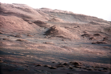 In this image released by NASA on Monday, Aug. 27, 2012, a chapter of the layered geological history of Mars is laid bare in this color image from NASA's Curiosity rover showing the base of Mount Sharp, the rover's eventual science destination. The image is a portion of a larger image taken by Curiosity's 100-millimeter Mast Camera on Aug. 23, 2012. Scientists enhanced the color in one version to show the Martian scene under the lighting conditions we have on Earth, which helps in analyzing the terrain. The pointy mound in the center of the image, looming above the rover-sized rock, is about 1,000 feet (300 meters) across and 300 feet (100 meters) high. (AP Photo/NASA/JPL-Caltech/MSSS)