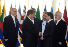 In this photo released by the official website of the Iranian presidency office, Iranian President Mahmoud Ahmadinejad, second right, welcomes Egyptian President Mohammed Morsi for the opening session of the Nonaligned Movement, NAM, summit, in Tehran, Iran, Thursday, Aug. 30, 2012. Morsi described the Syrian regime as