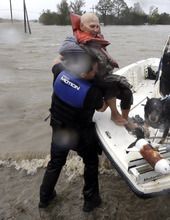 Elaine Maltese is lifted out of a boat by Drug Enforcement Agency Special Agent Keith Billiot, left, after being rescued from her flooded home as Hurricane Isaac hits Wednesday, Aug. 29, 2012, in Braithwaite, La. (AP Photo/David J. Phillip)