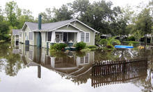 Flood waters surround a house in Slidell,.La. on Thursday, Aug. 30, 2012.  Isaac's maximum sustained winds had decreased to 45 mph and the National Hurricane Center said it was expected to become a tropical depression by Thursday night.  (AP Photo/John Bazemore)