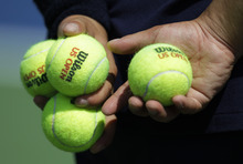 A ball person holds tennis balls during the second round of play at the 2012 US Open tennis tournament,  Thursday, Aug. 30, 2012, in New York. (AP Photo/Kathy Willens)