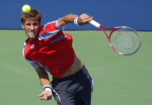 Slovakia's Martin Klizan returns a shot to France's Jo-Wilfried Tsonga in the second round of play at the 2012 US Open tennis tournament,  Thursday, Aug. 30, 2012, in New York. Fifth-seeded Tsonga was upset by Klizan in the second round. (AP Photo/Paul Bereswill)