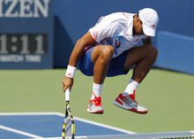 Jo-Wilfried Tsonga of France jumps over the net during his match against Slovakia's Martin Klizan in the second round of play at the 2012 US Open tennis tournament,  Thursday, Aug. 30, 2012, in New York. Fifth-seeded Tsonga was upset by Klizan in the second round. (AP Photo/Paul Bereswill)