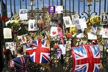 A man places a floral tribute for Britain's Princess Diana on the gate of Kensington Palace in London, on the 15th anniversary of her death, Friday, Aug. 31, 2012. Princess Diana was killed in a car accident in Paris in 1997. (AP Photo/Sang Tan)