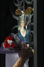 A supporter places a floral tribute for Princess Diana on the gate of Kensington Palace in London on the 15th anniversary of her death, Friday, Aug. 31, 2012. Princess Diana was killed in a car accident in Paris in 1997. (AP Photo/Sang Tan)