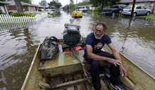 Milton is taken by boat from a flooded neighborhood, Thursday, Aug. 30, 2012, in Reserve, La. Isaac soaked Louisiana for yet another day and pushed more water into neighborhoods all around the city, flooding homes and forcing last-minute evacuations and rescues. (AP Photo/Eric Gay)