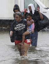 Residents evacuate their flooded neighborhood, Thursday, Aug. 30, 2012, in LaPlace, La. Isaac has caused major flooding in the region. Isaac staggered toward central Louisiana early Thursday, its weakening winds still potent enough to drive storm surge into portions of the coast and the River Parishes between New Orleans and Baton Rouge.  (AP Photo/Eric Gay)