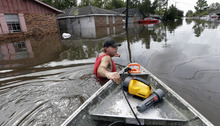 Frank Story walks a boat into a flooded community to help a friend recover items from his home, Friday, Aug. 31, 2012, in Reserve, La.  Isaac crawled into the central U.S. on Friday, leaving behind a soggy mess in Louisiana.  It will be a few days before the water recedes and people in flooded areas can return home. New Orleans itself was spared, thanks in large part to a levee system fortified after Katrina devastated the Gulf Coast in 2005. (AP Photo/Eric Gay)
