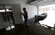 Christopher Tabb uses a boat to recover items from his flooded home, Friday, Aug. 31, 2012, in Reserve, La.  Isaac crawled into the central U.S. on Friday, leaving behind a soggy mess in Louisiana.  It will be a few days before the water recedes and people in flooded areas can return home. New Orleans itself was spared, thanks in large part to a levee system fortified after Katrina devastated the Gulf Coast in 2005. (AP Photo/Eric Gay)