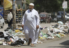 In this Thursday, Aug. 16, 2012 photo, a man walks in front of loads of garbage on a street in Cairo. A government modernization effort flopped. A swine flu panic prompted the mass slaughter of the pigs that recycled Cairo's organic garbage; the city's metal trash bins were easy prey for thieves, especially during the global scrap metal boom. Now the garbage crisis in the Arab world's biggest city is posing a significant test for the newly elected government that replaced longtime autocratic leaders. (AP Photo)