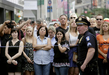 FILE - In this  Aug. 24, 2012, file photo, bystanders and a police officer stand on Fifth Avenue to view the scene outside the Empire State Building after a fatal shooting in New York. While recent shootings at a Colorado movie theater, a Sikh temple and outside the Empire State Building have grabbed headlines, residents of inner-city neighborhoods wracked by gun violence say they feel neglected and ignored in this presidential election year. (AP Photo/Mark Lennihan, File)