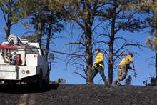 In this Saturday, Sept. 1, 2012 photo, Ralph Reece and Kelly Mansfield, of the Harrison Neb., volunteer fire department, work to put out hot spots along the Douthit wildfire near Crawford, Neb. Officials estimated Sunday that the fires have now burned roughly 273 square miles, including at least 27,000 acres in South Dakota. That's up from roughly 93 square miles on Saturday and more than twice the size of Omaha. (AP Photo/Omaha World-Herald, Mark Davis) MAGS OUT; ALL NEBRASKA LOCAL BROADCAST TV OUT