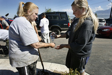 Scott Sommerdorf  |  The Salt Lake Tribune              Patti Robe, left and her daughter Karin Robe attempt to wash themselves off after they finished a shift volunteering to pitch in to help the homeowners affected by the flood near the intersection of Appaloosa and Weatherby Drives in Saratoga Springs, Sunday, September 2, 2012.