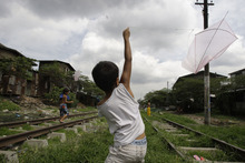 A Filipino boy flies his kite as they play along the railroads in suburban Manila, Philippines on Sunday Sept. 2, 2012. (AP Photo/Aaron Favila)