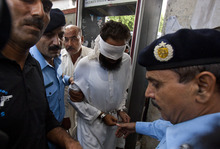 Pakistani police officers escort blindfolded Muslim cleric Khalid Chishti to appear in court in Islamabad, Pakistan, Sunday, Sept. 2, 2012. In the latest twist in a religiously charged case that has focused attention on the country's harsh blasphemy laws, Pakistani police arrested Chishti who they say planted evidence in the case of a Christian girl accused of blasphemy. (AP Photo/Anjum Naveed)
