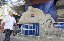 A man walks near a sand sculpture created in the likeness of President Barack Obama in downtown, Sunday, Sept. 2, 2012, in Charlotte, N.C.  (AP Photo/Chuck Burton)