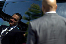 Secret Service agents stand guard as Republican presidential candidate, former Massachusetts Gov. Mitt Romney walks to his car after services at the Church of Jesus Christ of Latter-day Saints on Sunday, Sept. 2, 2012 in Wofeboro, N.H.  (AP Photo/Evan Vucci)
