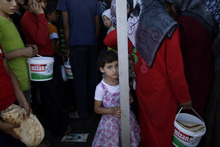 A Syrian girl, bottom center, who fled her home, due to fighting between the Syrian army and the rebels, waits her turn to buy bread and eggs from a store, as she and others take refuge at the Bab Al-Salameh border crossing, in hopes of entering one of the refugee camps in Turkey, near the Syrian town of Azaz, Monday, Sept. 2, 2012. (AP Photo/Muhammed Muheisen)
