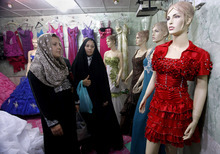 In this Sunday, Sept 2, 2012 photo, Iraqi women shop at a women's fashion store in Diwaniyah, 130 kilometers (80 miles) south of Baghdad, Iraq, Sunday, Sept 2, 2012. A new culture rift is emerging in Iraq, as young women replace shapeless cover-ups with ankle-baring skirts and tight blouses, while men strut around in revealing slacks and spiky haircuts. The relatively skimpy styles have prompted Islamic clerics in at least two Iraqi cities to mobilize the