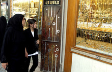 In this Sunday, Sept 2, 2012 photo, Iraqi women look at jewelry at a market in Kazimiyah neighborhood, Bagdad, Iraq. A new culture rift is emerging in Iraq, as young women replace shapeless cover-ups with ankle-baring skirts and tight blouses, while men strut around in revealing slacks and spiky haircuts. The relatively skimpy styles have prompted Islamic clerics in at least two Iraqi cities to mobilize the