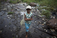 A boy with tattoos on his arms walks in a slum area in Yangon, Myanmar, Monday, Sept. 3, 2012. (AP Photo/Alexander F. Yuan)