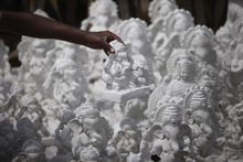An artist places an idol of the elephant-headed Hindu god Ganesh, for sale for the upcoming Ganesh Chaturthi festival, in Jammu, India, Monday, Sept. 3, 2012. The idols will be immersed in rivers at the end of the festival.(AP Photo/Channi Anand)