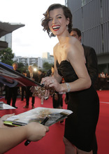 Actress Milla Jovovich signs autographs on her arrival at the World premiere of