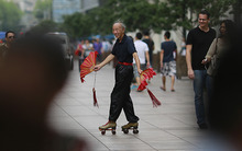 A street artist performs on a pedestrian street Monday Sept. 3, 2012 in Shanghai, China. (AP Photo/Eugene Hoshiko)