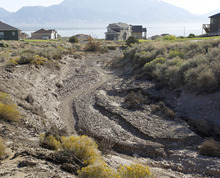 Al Hartmann     The Salt Lake Tribune The normally dry wash in the Jacobs Ranch subdivision is filled with mud and debris from Saturday's flash flood and mud flow.   Some of the houses to the side of the wash were damaged by the mud flow that ran down the wash to the flood-retention basin below.