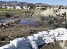 Al Hartmann     The Salt Lake Tribune Sandbags still line the flood-retention basin in the Jacobs Ranch subdivision in Saratoga Springs on Tuesday, Sept. 4.  The basin is full of mud from Saturday's flash flood and mud flow.