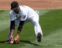 Kim Raff | The Salt Lake Tribune Salt Lake Bees third baseman Luis Jimenez scoops up a bunt during a  game agasint the Fresno Grizzlies at Spring Mobile Ballpark in Salt Lake City on July 22, 2012.