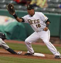 Trent Nelson  |  The Salt Lake Tribune Bees first baseman Efren Navarro fields the pick-off attempt as Reno's Jake Elmore dives back to first, at Salt Lake Bees vs. Reno Aces baseball Friday, April 27, 2012 at Spring Mobile Ballpark in Salt Lake City. Elmore was called safe on the play.
