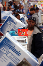 Jazzmine Cotton, 13, stands in a long line at the layaway counter at a Wal-Mart store in Denver, Colorado, early Friday morning, November 29, 2002. Discounts at Wal-Mart Stores Inc. and Federated Department Stores Inc. drew customers and bolstered sales for U.S. retailers in the first weekend of the holiday-shopping season.  Photographer: Matthew Staver/Bloomberg News