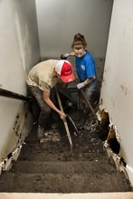 Douglas C. Pizac  |  Special to The SAlt Lake Tribune  Volunteers Whitley Peterson, 15, and Shellee Larsen, 14, shovel mud off the stairs leading down to the basement during the cleanup of a home flooded by hillside run off Monday, Sept. 3, 2012, in Saratoga Springs, Utah.  The entire basement was filled with muck up to the second from the top stair, bottom.