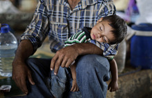 Syrian, Ghassan Khalil, 30, who fled his home in Marea 12 days ago due to Syrian government shelling of his house, holds his sleeping son Mahmoud, 2, who suffers from fever, as they take refuge at the Bab Al-Salameh border crossing in hopes of entering one of the refugee camps in Turkey, near the Syrian town of Azaz, Monday, Sept. 3, 2012. (AP Photo/Muhammed Muheisen)
