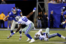 New York Giants quarterback Eli Manning (10) scrambles against Dallas Cowboys linebacker DeMarcus Ware (94) and Gerald Sensabaugh (43) during the first half of an NFL football game Wednesday, Sept. 5, 2012, in East Rutherford, N.J. (AP Photo/Bill Kostroun)