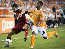 Real Salt Lake defender Tony Beltran, left, fights to control the ball against Houston Dynamo midfielder Corey Ashe during an MLS soccer match, Thursday, Sept. 6, 2012, in Houston. (AP Photo/Houston Chronicle, Smiley N. Pool)  MANDATORY CREDIT