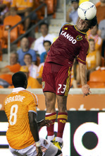 Real Salt Lake forward Paulo Jr. (23) heads the ball over Houston Dynamo defender Kofi Sarkodie (8) during an MLS soccer match, Thursday, Sept. 6, 2012, in Houston. (AP Photo/Houston Chronicle, Smiley N. Pool)  MANDATORY CREDIT