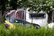 An investigator enters the trailer where the slain British family were holidaying in a camp site of Saint Jorioz, near Annecy, France Thursday, Sept. 6, 2012. A 4-year-old British girl hid for eight hours beneath the bodies of slain family members in the back of their car in a nearby forest, before she was discovered by French investigators who had been guarding the vehicle, a prosecutor said Thursday. Three people — a man and two women — had been shot to death, as was a French cyclist whose body was found nearby  (AP Photo/Lionel Cironneau)