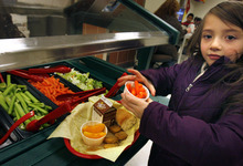Scott Sommerdorf  l  Tribune file photo Mia Love's budget-balancing plan calls for cutting federal subsidies for the school lunch program. In this file photo from last year, young Serenity Ward chooses carrots and peaches from the salad bar to go with her choice of chicken nuggets and chocolate milk for her school lunch at Woodrow Wilson Elementary School.