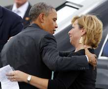 President Barack Obama embraces an unidentified guest as he arrives at the Charlotte/Douglas International Airport for the Democratic National Convention in Charlotte, N.C., Wednesday, Sept. 5, 2012. (AP Photo/Chuck Burton)