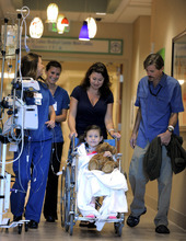 Seven-year-old Sierra Jane Downing from Pagosa Springs, Colo., is pushed to a news conference about her recovery from Bubonic Plague by her mother Darcy and father Sean Downing along with nurses  at the Rocky Mountain Hospital for Children at Presbyterian/St. Luke's Wednesday, Sept. 5, 2012, in Denver. It is believed Downing caught the Bubonic Plague from burying a dead squirrel. (AP Photo/Jack Dempsey)