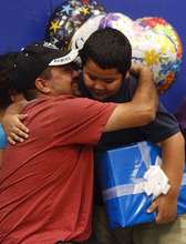Leah Hogsten  |  The Salt Lake Tribune Edison Elementary third-grader Abraham Vega receives a hug and a kiss from his father, Jesus Vega, on Thursday after Abraham was given a  netbook computer from Comcast for most improved language arts score in his class. Edison Elementary students learned more about the benefits of connecting to the Internet with hands-on Internet training, an introduction to accessing and reading e-books online and how the use of multi-faceted document cameras donated to the school by Comcast will help improve the education experience for students and teachers.